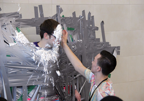 Junior Kaden Demedeiros, a member of the Entrepreneurship class, wipes Markley's goggles of whipped cream after he took several pies to the face. Photo by Journey Robison