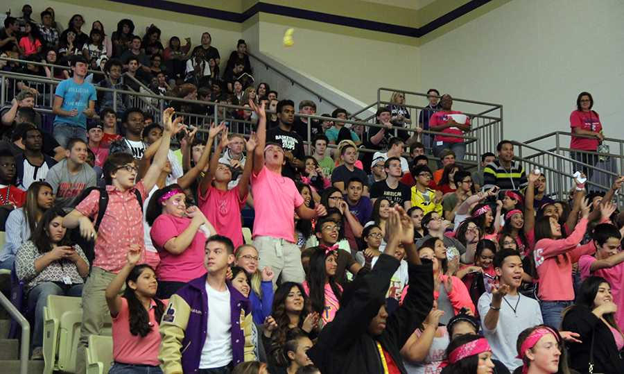 Dressed in pink, several students reach for the candy from the cheerleaders at the unofficial Pink Out pep rally Oct. 10. The