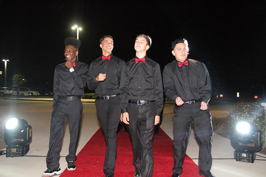In matching outfits, juniors Donavin Arin, Tra'vel Davis, sophomore Matthew Powell, and junior Josh Rodriguez put on a show for the paparazzi at the dance red carpet. Photo by Nick Alvarez