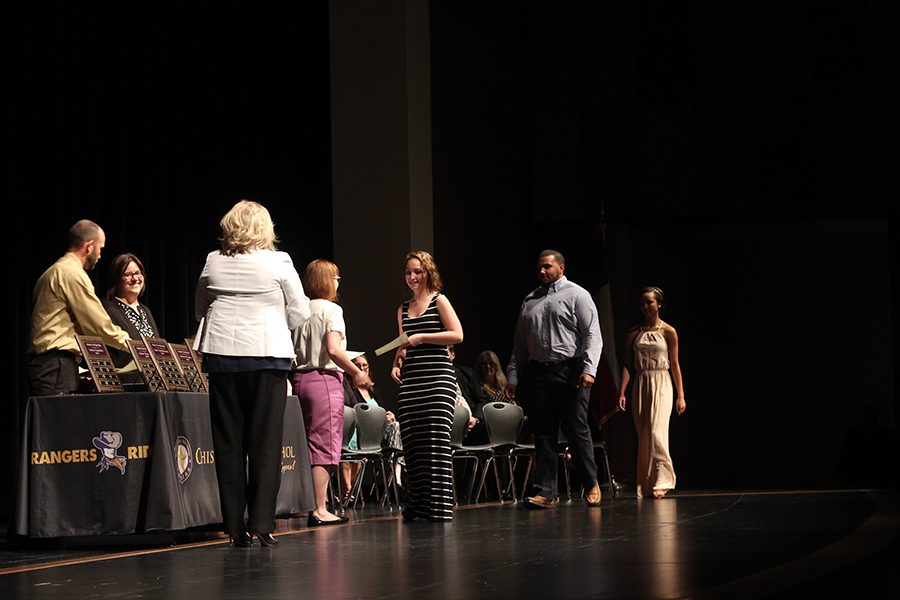 Seniors Ellen Hamzy, Kenny Hill, and Jada Martin walk on stage to receive Outstanding Student Awards for Social Studies from Department Chair Jennifer Hamzy.