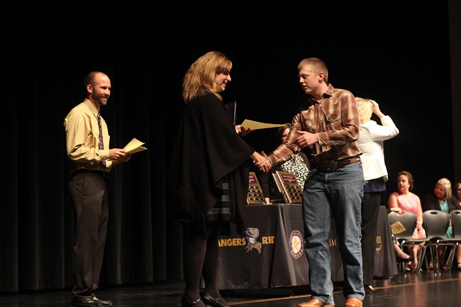 Senior Dylan Lofton shakes hands with Board Vice President Paige Ring as she hands him the certificate for the EMS-ISD scholarship.