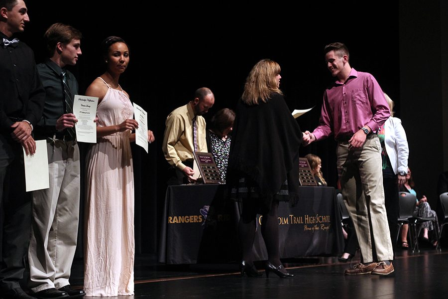 Senior Michael May shakes hands with Board Vice President Paige Ring as he receives his certificate for his EMS-ISD scholarship.