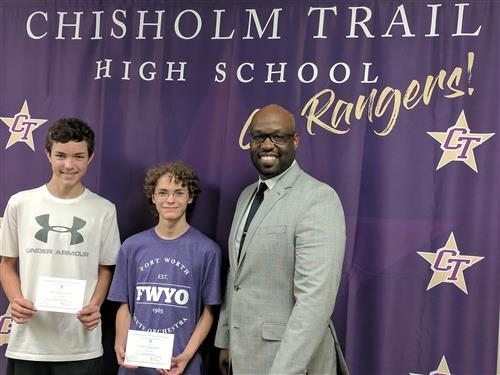 Logan Miertschin and Justyn Epps stand with Principal Berringer as they recieve their letters of Commendation from the National Merit Scholarship Corporation.