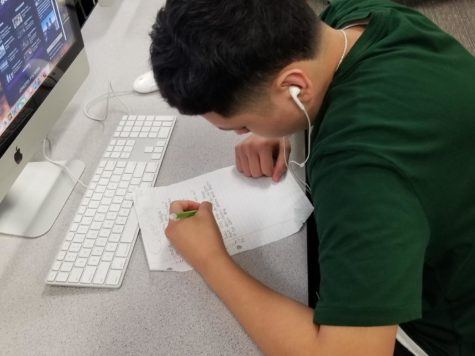 Freshman Cristian Navarro works in second period journalism class.