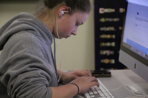 Creative Writing Club President Hannah Moore works on her novel during a club meeting.